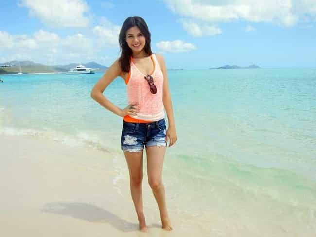 Med henne smal kropp och Mörk brun hårtyp utan behå (kupstorlek 34B) på stranden i bikini
