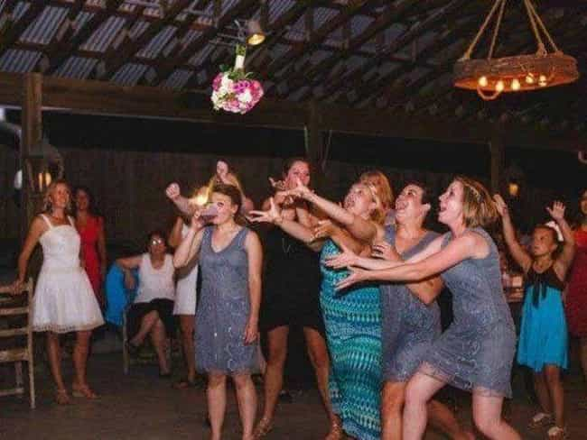 A Woman with Her Priorities in... is listed (or ranked) 4 on the list Amazing Wedding Bouquet Toss Moments Caught on Film