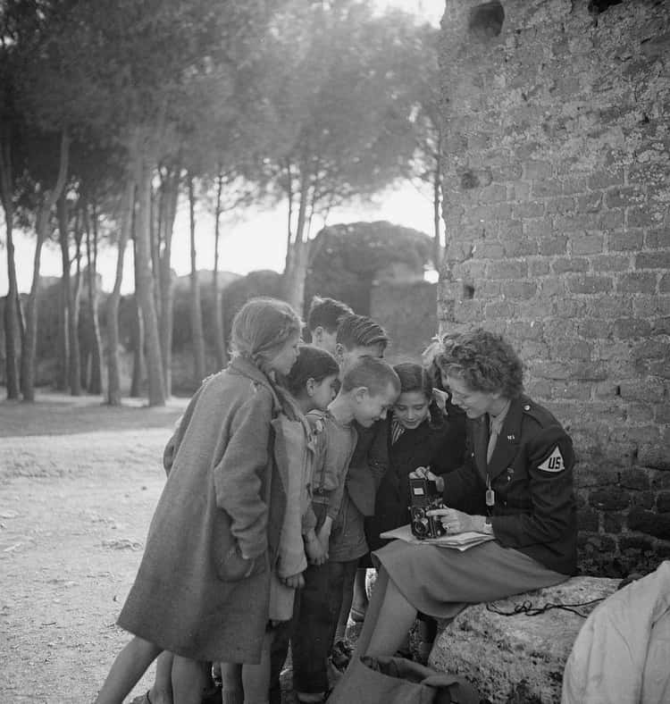 WWII Photographer Toni Frissell Showing Her Camera To Children In Europe (1945)